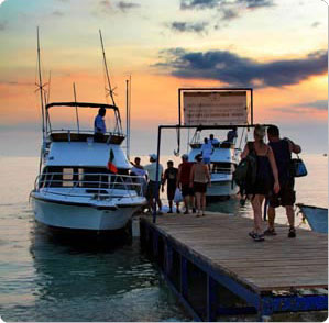 Guests at Hotel Buena Vista Beach Resort make their way to fishing charter boats early in the morning.